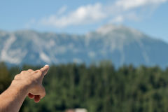 Male hand showing destination on the mountain Royalty Free Stock Photo