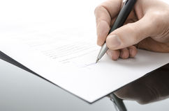 Male hand signing a contract on a black table Stock Photography