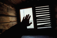 Male hand silhuette over small grungy window. Male hand silhouette over small grungy window with shutters Stock Images