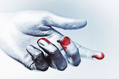 Male hand in silver paint with drops of blood Stock Images