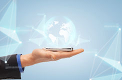 Male hand with smartphone and globe projection Stock Image