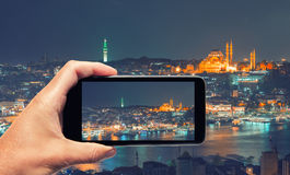 Male hand with smartphone taking a picture of Istanbul at night. Royalty Free Stock Images