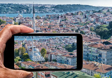 Male hand with smartphone taking a picture of Istanbul. Tourism Stock Photo