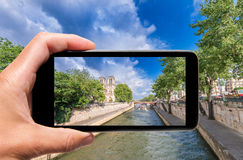 Male hand with smartphone taking a picture of Paris and Notre Da Royalty Free Stock Images