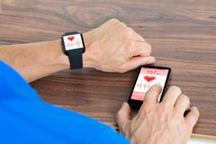 Male hand with smartwatch and cellphone Royalty Free Stock Photography