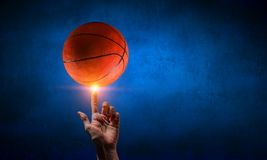 Basketball game concept. Male hand spinning basketball bal on finger Stock Photography