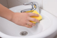 Male hand with sponge cleaning sink Royalty Free Stock Photography