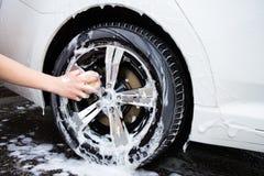 Male hand with sponge washing car wheel Stock Photo