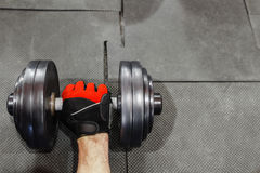 Male hand in sport glove holding dumbbell void Stock Photography