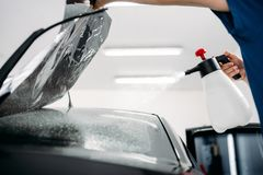 Male hand with spray, car window tint installation Royalty Free Stock Photography