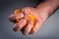 Male hand squeezing orange. Stock Photos