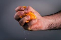 Male hand squeezing orange. Royalty Free Stock Photos