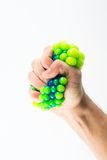 Male hand squeezing stress ball. Over plain background Stock Images