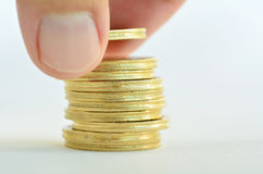 Male hand stacking gold coins Stock Image