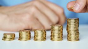 Male hand stacking gold coins into increasing columns stock footage