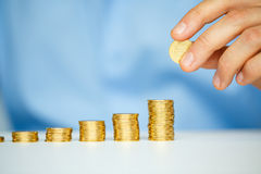 Male hand stacking gold coins into increasing columns Royalty Free Stock Photography