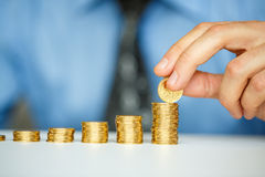Male hand stacking gold coins into increasing columns Royalty Free Stock Image