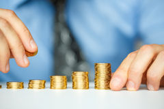 Male hand stacking gold coins into increasing columns Stock Photos