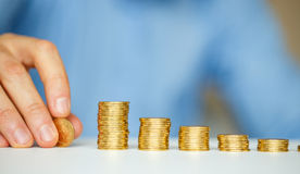 Male hand stacking gold coins into increasing columns Stock Photo