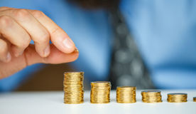 Male hand stacking gold coins into increasing columns Stock Images