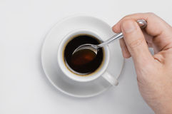 Male hand stir slowly black coffee with spoon in coffee cup against white background with place for text top view. Male hand stir slowly black coffee with spoon royalty free stock photography
