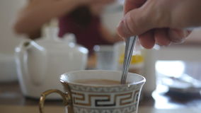 Male hand stirring sugar or milk in a cup of hot coffee or tea. Slow motion Close up stock video