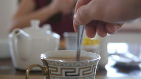 Male hand stirring sugar or milk in a cup of hot coffee or tea. Slow motion Close up.  stock video