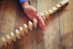 A male hand stoping the domino effect. retro style image executive and risk control concept Royalty Free Stock Photography