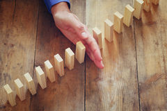 A male hand stoping the domino effect. retro style image executive and risk control concept Stock Photography