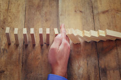 A male hand stoping the domino effect. retro style image executive and risk control concept Stock Photo