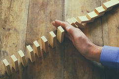 A male hand stoping the domino effect. retro style image executive and risk control concept Royalty Free Stock Images