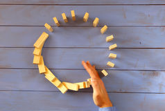 A male hand stopping the domino effect. retro style image executive and risk control concept Royalty Free Stock Photos