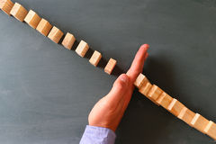 A male hand stopping the domino effect Royalty Free Stock Photos