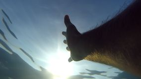 Male hand stretches from under the water to sunrays. Arm asking for help and trying to reach to the sun. Point of view stock footage
