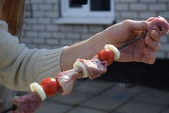 Male hand strings pork meat on skewer stock photography