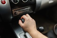 Male hand switches automatic transmission closeup. Close up view of gear lever manual transmission car interior parts royalty free stock images