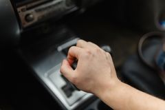 Male hand switches automatic transmission. Closeup. Close up view of gear lever manual transmission car interior parts stock image