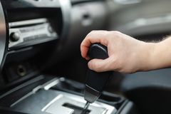 The male hand and switches the transmission. A view of the Assembly of The male and switches the automatic transmission`s close-up. Close-up of the driver`s adm royalty free stock photography