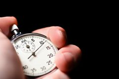 Male hand starts the analog stopwatch on a black background, close-up, isolate, copy space royalty free stock photo