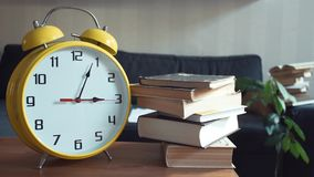 Male hand takes the book off the shelf. Big yellow clock is ticking