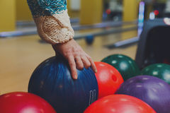 Male hand taking ball from bowling machine Royalty Free Stock Image