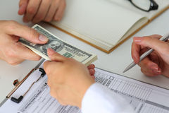 Male hand taking or giving bunch of hundred dollars bank notes Stock Image