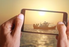 Male hand taking photo of a boat in the sea in sunset with cell, mobile phone. Stock Images