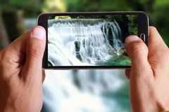 Male hand taking photo of a green rock mountain with a waterfall landscape with cell, mobile phone. Stock Photos