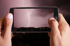 Male hand taking photo of lightning in the city lanscape with cell, mobile phone. Stock Photo