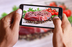 Male hand taking photo of Raw beefsteak with spices and cherry tomatoes on wooden background with cell, mobile phone. Stock Photo