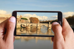 Male hand taking photo of river Tiber from the bridge in Rome with cell, mobile phone. Italian holiday. Stock Photos