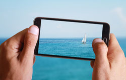 Male hand taking photo of Sailboat, sea, sun, blue, sea, horizon and ocean with cell, mobile phone. Stock Photography
