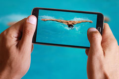 Male hand taking photo of Strong athletic man swimming butterfly style in the pool with cell, mobile phone. Royalty Free Stock Photo