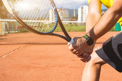 Male hand with tennis racket. Closeup photo of male hand with tennis racket hitting the ball Royalty Free Stock Image